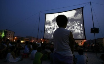 People watch a free movie at an open-air cinema at a square after an earthquake in Wen'an County, Hebei Province of China on July 4, 2006.