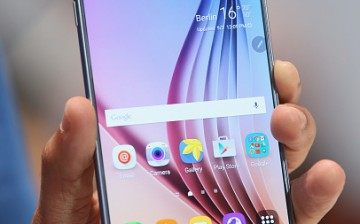 A visitor holds a Galaxy Note 5 smartphone at the Samsung stand in 2015.