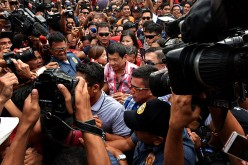 Presidential candidate Rodrigo Duterte (center) flocked by supporters and members of the media while on his way to cast his vote in a polling precinct on May 9, 2016 in Davao City, Philippines.