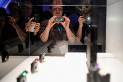People take photos of a Sony Playstation 4, not the PlayStation NEO, and its controllers on display