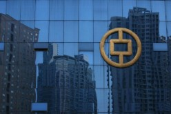 Buildings under construction are reflected on glass at the People's Bank of China office building on Sept. 29, 2007 in Chongqing, China.