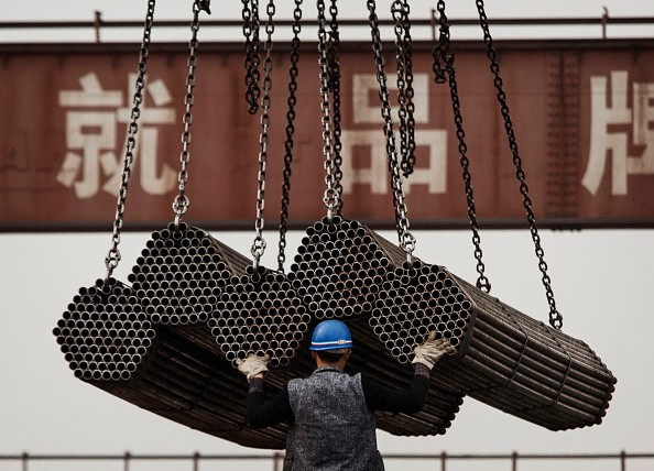 A Chinese steel worker helps load steel rods onto a large truck for transport at a plant on April 6, 2016 in Tangshan, Hebei province, China.