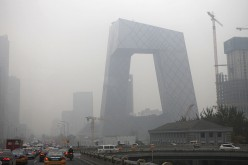 Vehicles move on the street early morning in heavy smog in front of the CCTV headquarters on Nov. 12, 2015 in Beijing, China.