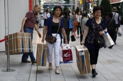 Chinese tourists carry packages of Panasonic Corp.'s washlet along Tokyo's Ginza Shopping District on May 16, 2014.