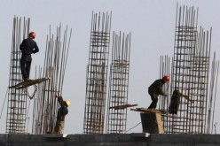 Construction workers lay the foundation for a new apartment building in Henan Province.