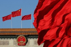 Red flags flutter in the wind near the Chinese national emblem outside the Great Hall of the People.