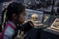 A Chinese girl walks past a skull said to be that of a villager killed by Japanese troops in the Second World War during a visit to a WWII museum on Sept. 1, 2015 in Beijing, China.