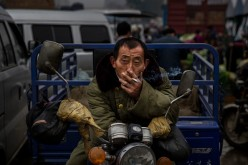 A Chinese laborer smokes a cigarette at a local market on Sept. 26, 2014 in Beijing, China.