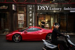 A Chinese man stands next to his luxury car as its is parked in an upscale shopping district on May 29, 2015, in Beijing, China.