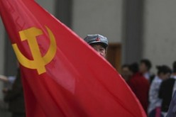 A member of China's Communist Party waves a flag during a gathering in Kunming, Yunnan Province.
