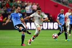 Uruguay defender Diego Godin (L) competes for the ball against Mexico's Hector Herrera.