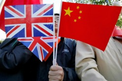 A Chinese man holds British and Chinese flags on Nov. 9, 2005, in London, England.