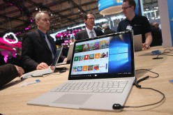 Visitors check out the Surface Book laptop at the Microsoft stand at the 2016 CeBIT digital technology trade fair on the fair's opening day on March 14, 2016 in Hanover, Germany.
