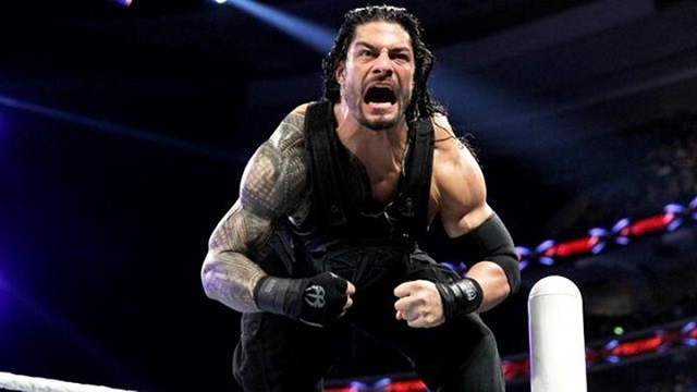 Roman Reigns flexes his muscles before a wrestling match.