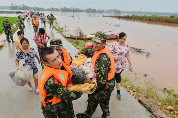 Rescuers evacuate residents from flood-hit areas in Chongqing, China, in this July 2, 2013 photo.