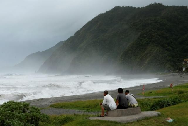Men watch waves crash at the coast as Typhoon Nepartak approaches in Yilan, Taiwan, July 7, 2016.