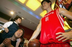 A visitor and his daughter view the waxwork of NBA star Yao Ming at Madame Tussauds Shanghai on May 1, 2006, in Shanghai, China.