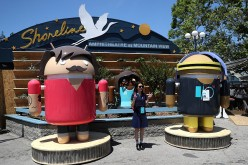 An attendee poses for a photo next to Android characters during Google I/O 2016 at Shoreline Amphitheatre on May 19, 2016 in Mountain View, California.