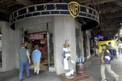 People walk by a statue of cartoon character Bugs Bunny, dressed as a fisherman, outside of a Warner Bros. Studio Store.