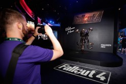 A game enthusiast takes a photograph of a 'Mr. Handy' robot in promotion to 'Fallout 4' at the Annual Gaming Industry Conference E3 at the Los Angeles Convention Center.