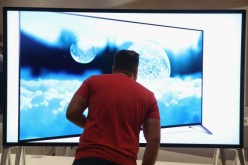 A visitor looks at a 4000K television at the Sony stand at the 2014 IFA home electronics and appliances trade fair.