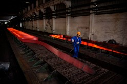 A worker walks past a hot roller steel at a steel manufacturing plant in Changzhou, Jiangsu Province.