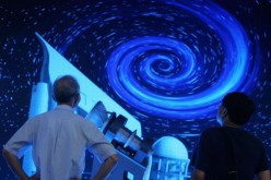 Visitors view a model of the large sky area multi-object fiber spectroscopic telescope (LAMOST) at the Shenzhen Convention & Exhibition Center on Oct. 13, 2006.