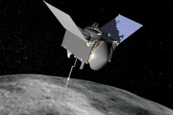 An artist's rendition of the OSIRIS-REx spacecraft hovering over Bennu the asteroid.