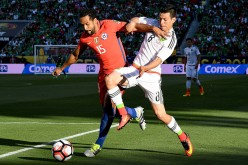 Mexico striker Hirving Lozano (R) competes for the ball against Chile's Jean Beausejour.