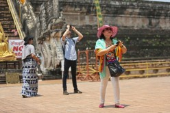 Chinese tourists take pictures at Wat Chedi Luang on April 17, 2014, in Chiang Mai, Thailand.