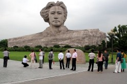 Face-to-face: Tourists gather near the bust of a young Mao Zedong and his wind-blown hair in Orange Isle in Changsha, Hunan Province. The isle loses its 5A tourist attraction rating this month.