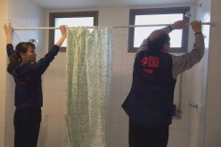 Members of the Chinese gymnastics team putting the shower curtains in their quarters at the Olympic Village in Rio.