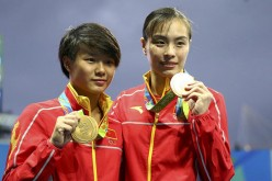 Chinese diving athletes Wu Minxia and Shi Tingmao show gold medals at the awarding ceremony of women's SYNC.3M Springboard in Rio on Sunday.