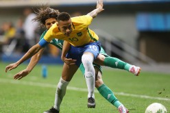 Brazil forward Neymar competes for the ball against an Iraqi defender.