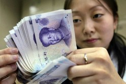 A bank employee counts new 5-yuan (60 U.S. cents) bank notes in Beijing.