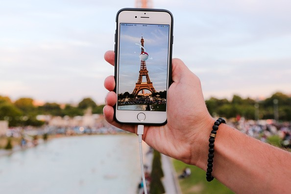 A man catches a Pokemon in a Pokeball, while playing Nintendo Co.'s Pokemon Go augmented-reality game at the Trocadero, in front of the Eiffel tower, on August 17, 2016 in Paris, France.