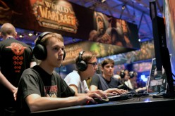 Visitors try out the massively multiplayer online role-playing game 'World Of Warcraft' at the Blizzard Entertainment stand at the 2014 Gamescom gaming trade fair on August 14, 2014 in Cologne, German