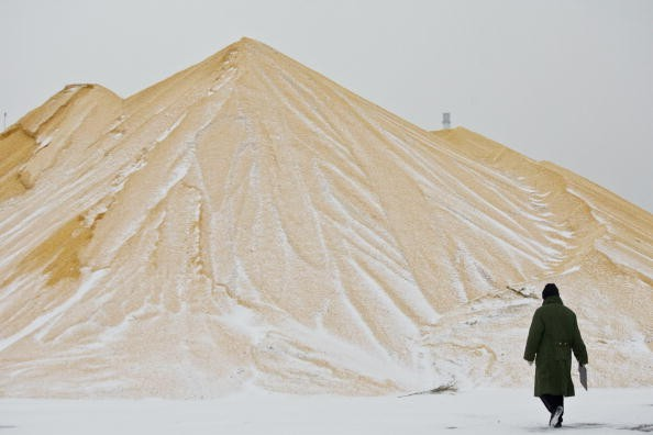 A farmer walks past a pile of corn at a state grain reserves depot on Dec. 19, 2008, in Yushu in Jilin Province, China.