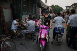 A Chinese man riding on his electric scooter passed a group of men eating at an outdoor restaurant on May 27, 2015 in Beijing, China.