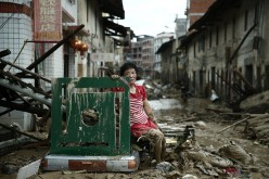 A woman sits amid the destruction left behind by Typhoon Nepartak in China.