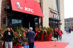 People walk in front of a KFC fast food restaurant in Lhasa, Tibet Autonomous Region.