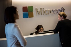 Employees walk past the reception booth of Microsoft's new office in Hong Kong.