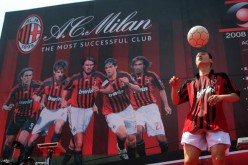 A soccer fan performs football skills in front of a billboard featuring AC Milan players on May 10, 2008 in Nanjing of Jiangsu Province, China.