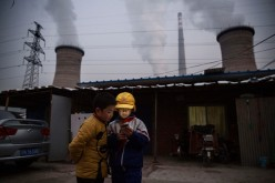 Chinese boys look at their smartphone in front of their house next to a coal-fired power plant on Nov. 27, 2015, on the outskirts of Beijing, China.