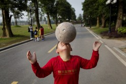 A young Chinese student balances the ball on his nose as he walks to a training match at the Evergrande International Football School on June 14, 2014, near Qingyuan in Guangdong Province, China.