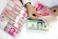 A clerk counts stacks of Chinese yuan and U.S. dollars at a bank on July 22, 2005, in Shanghai, China.