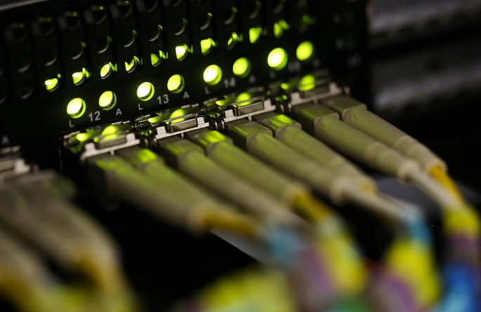 Fiber-optic cables are attached into a server inside a communications room in London.