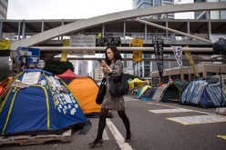 A businesswoman walks past tents used by pro-democracy protesters at the Admiralty protest site on Nov. 13, 2014 in Hong Kong, Hong Kong.