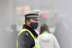 A policeman wears a face mask while directing traffic on Dec. 9, 2015, in Taiyuan, Shanxi Province of China.