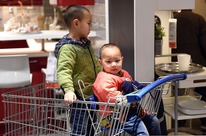 Don't worry I've got your back: Two boys keep each other company at a furniture store in Beijing, on Jan. 19, 2015.